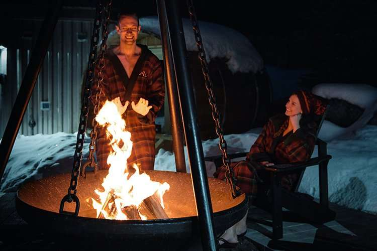 couple sitting by fire cauldron at night